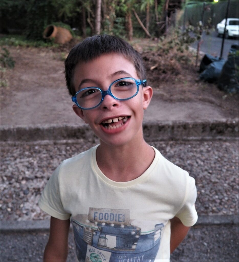 Boy smiling with blue glasses.