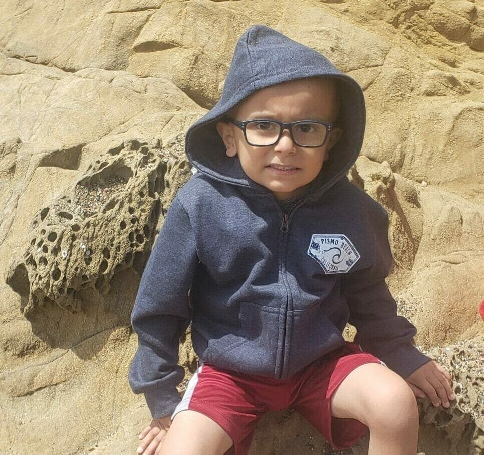 Kid with a concerned smile sitting on rocks