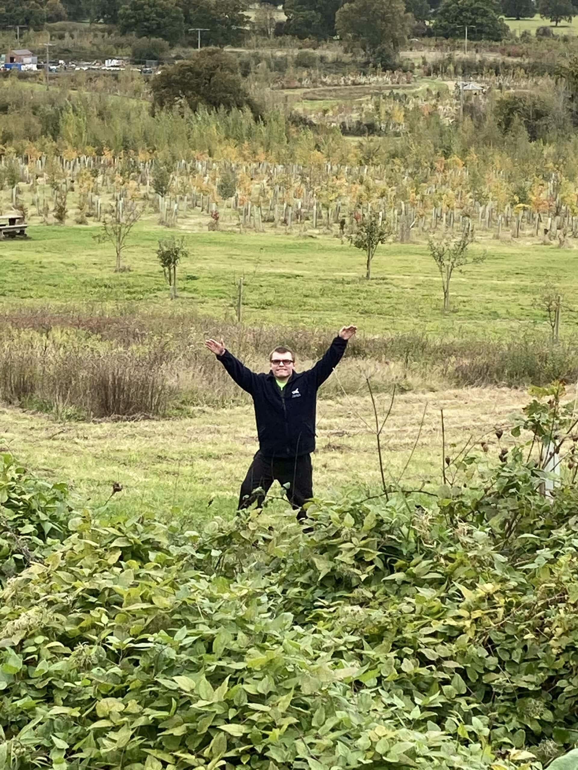 Teen with his arms raised in a field