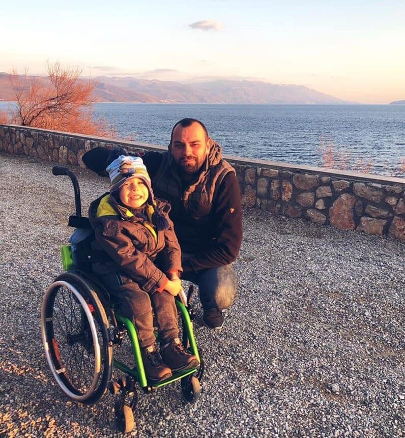 Boy in a wheelchair next to a lake