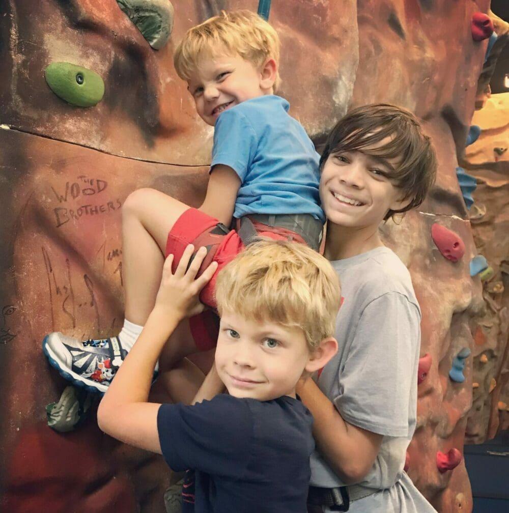 Boys helping on climbing wall.