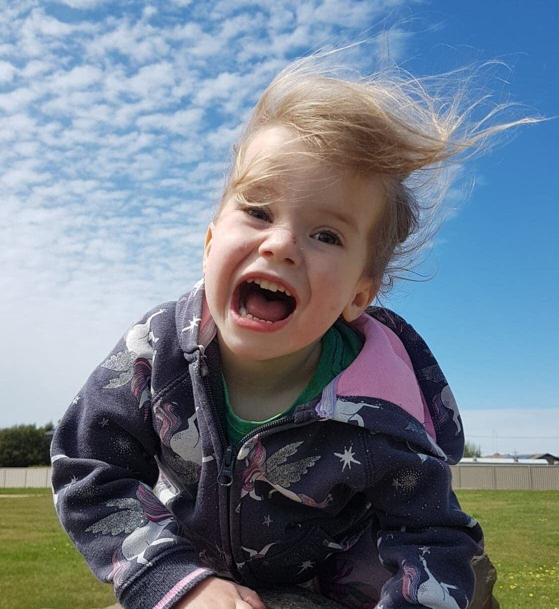 Little girl with huge smile and clouds.