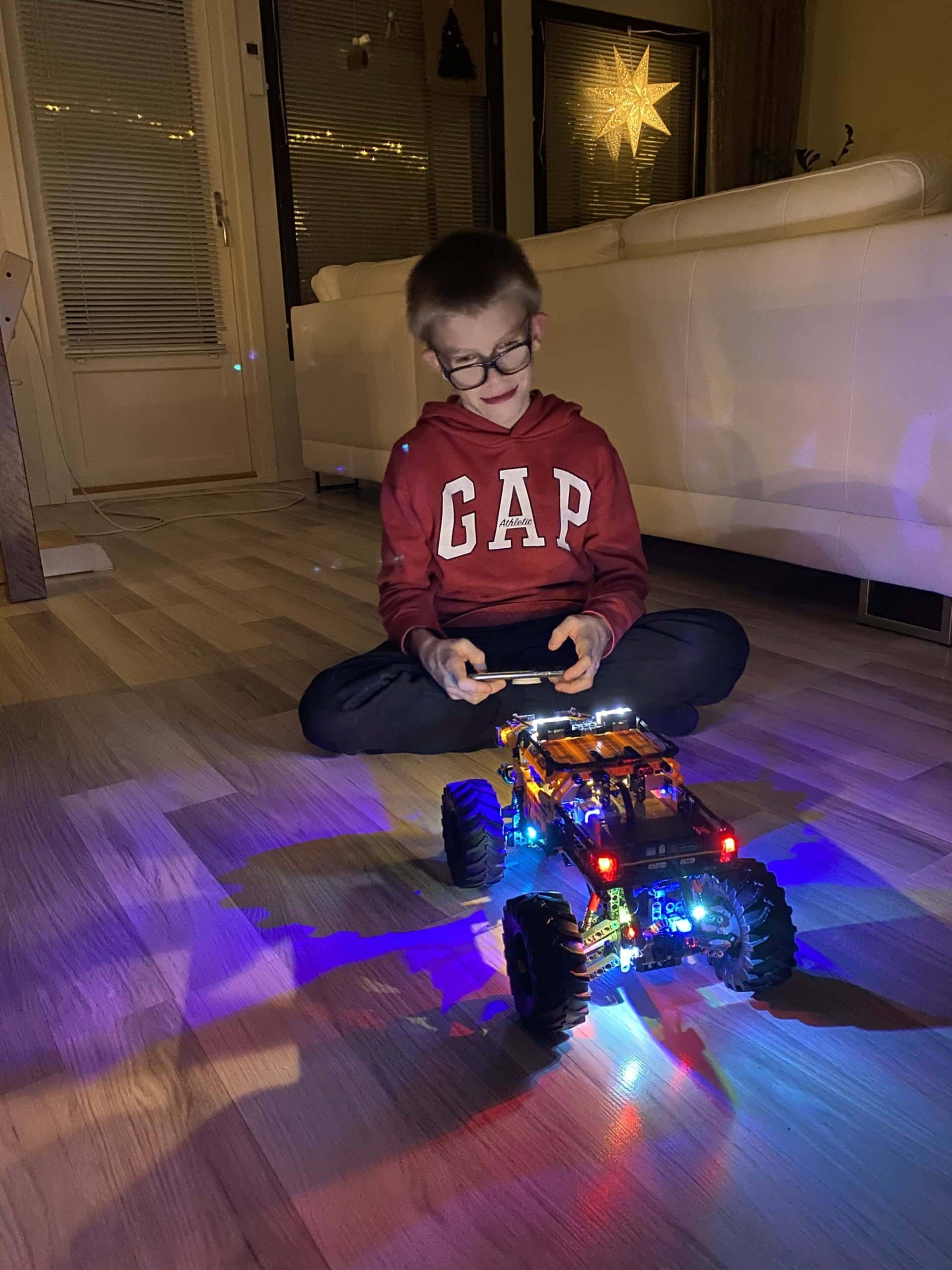 Kid sitting in the dark playing with a light up remote car