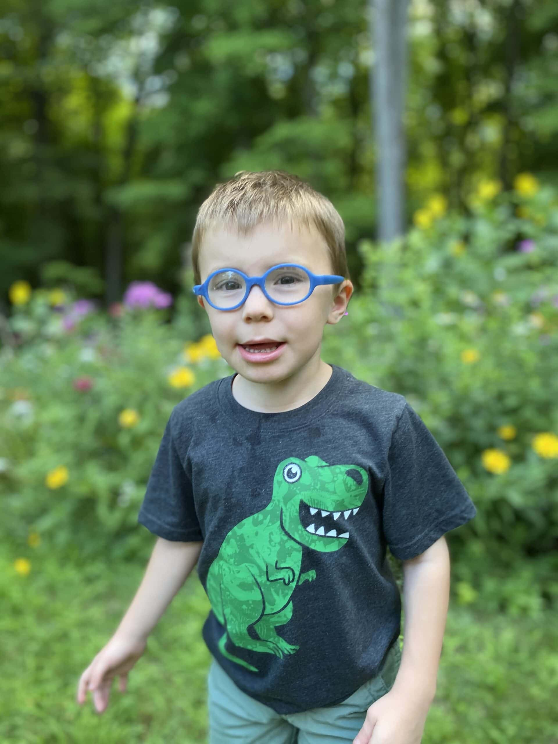 Small kid with glasses, smiling at the camera