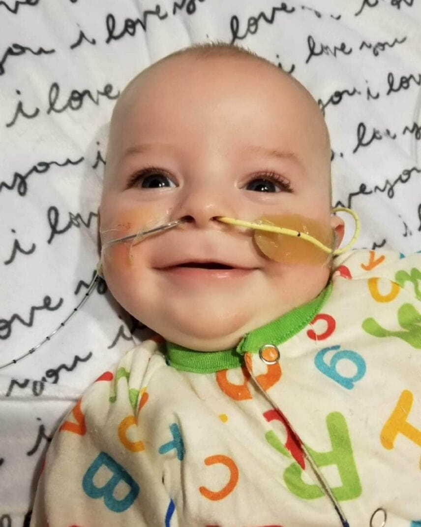 Smiling baby with oxygen in their nose