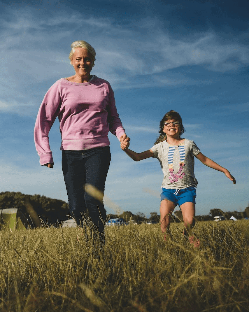 Parent and child holding hands in a field
