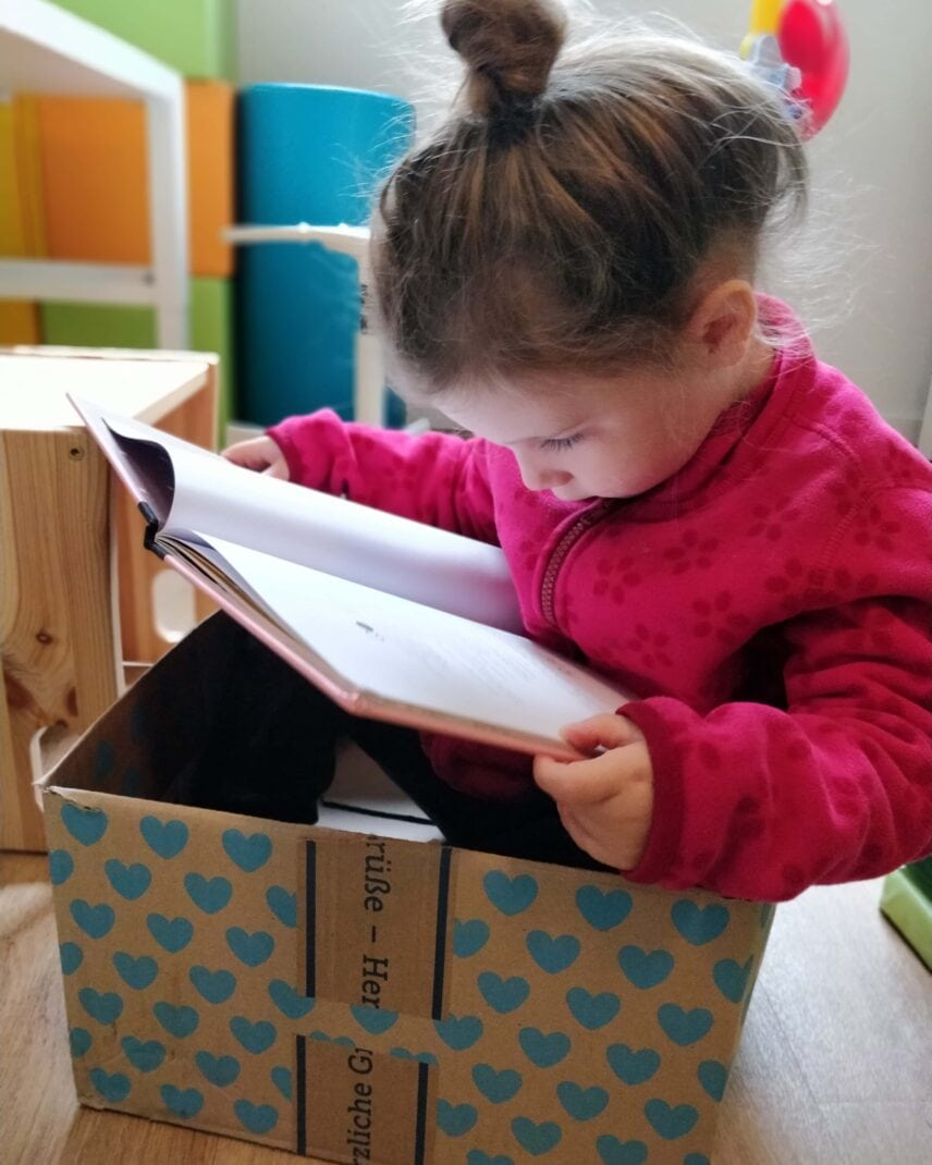Sweet girl in a box, reading a book